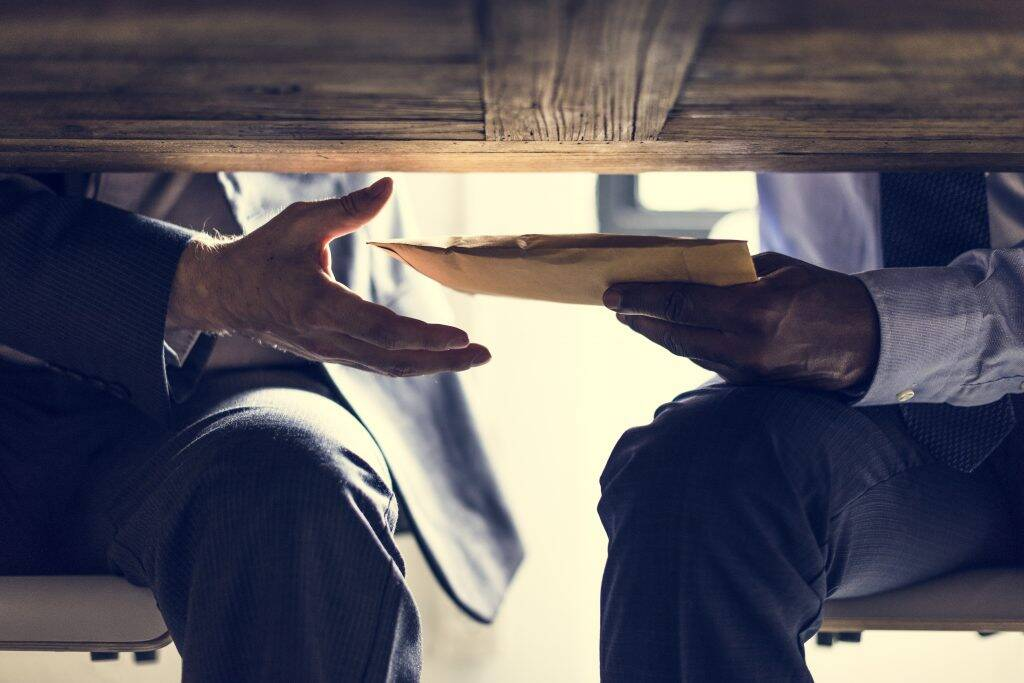business-people-sending-documents-under-the-table-PB2TXRA-1024x683
