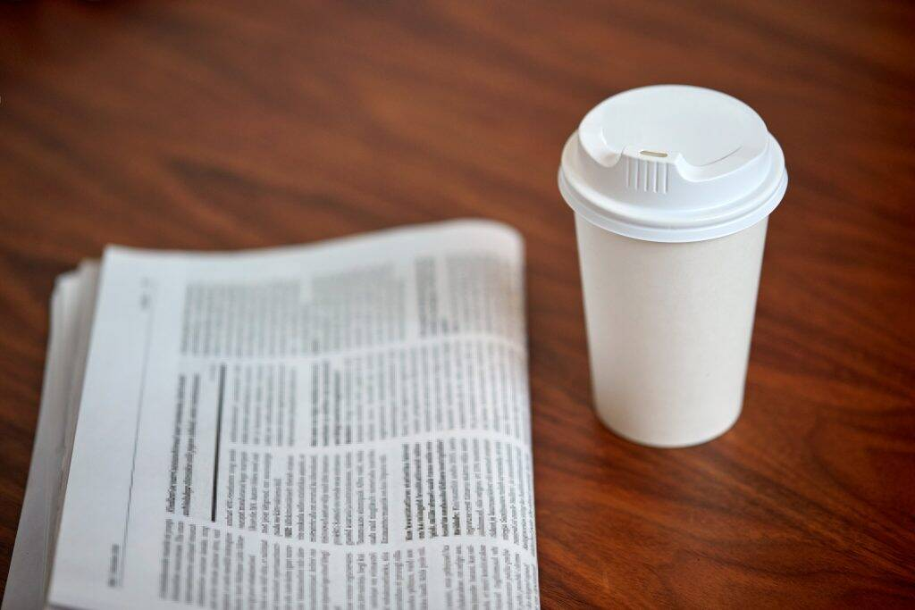 coffee-drink-in-paper-cup-and-newspaper-on-table-PWT4US7-1024x683