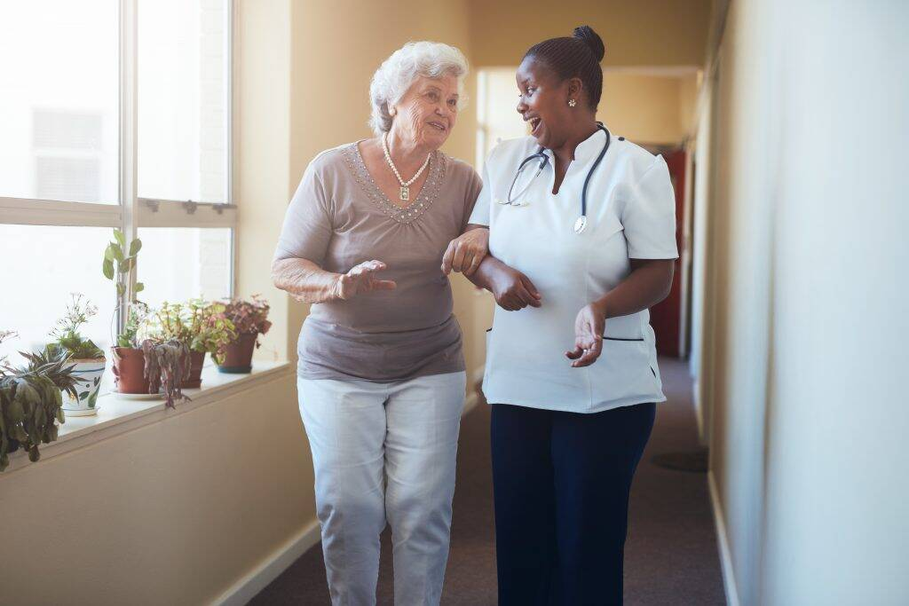 happy-healthcare-worker-walking-and-talking-with-s-P9FVKDL-1024x683