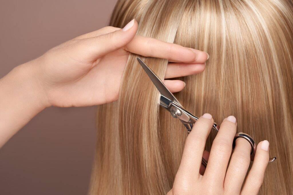 hairdresser-cuts-long-blonde-hair-with-scissors-ACPEBSN-1024x683