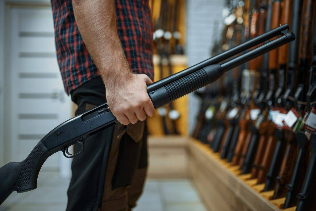 male-person-with-rifle-at-showcase-in-gun-shop-PP65Q2K-1024x684