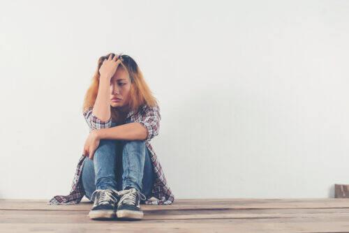 Femme toute seule et triste qui se fait un calin des genoux assis sur le sol d'une piece vide